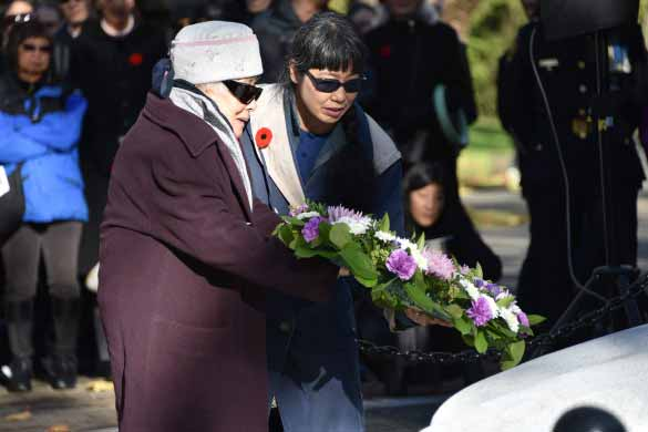 Kazuko Yatabe lays a wreath in memory of her husband. Randy Enomoto photo.